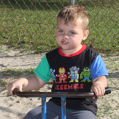 photo of 3 year old riding tricycle on playground